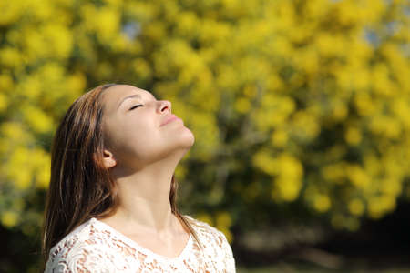 closed eye: Woman breathing deep in spring or summer with a yellow background
