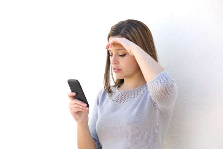 urgent: Worried woman looking at the mobile phone on a white wall isolated