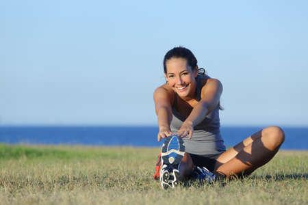 personas trotando: Corredor de la mujer de la aptitud que estira en la hierba con el mar y el horizonte en el fondo