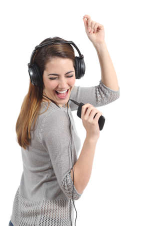 Funny woman with headphones dancing singing and listening to the music from a smart phone isolated on a white background photo