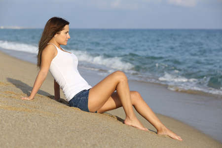 Beautiful woman sitting on the sand of the beach watching the sea with the horizon in the background photo