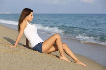 mujer mirando el horizonte: Hermosa mujer sentada en la arena de la playa mirando el mar con el horizonte en el fondo Foto de archivo