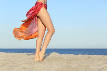 treatment: Standing woman legs posing on the beach wearing a pareo with the horizon in the background