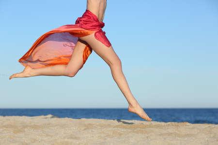piedi nudi di bambine: Gambe di donna che saltano sulla spiaggia felice con l'orizzonte e il mare sullo sfondo