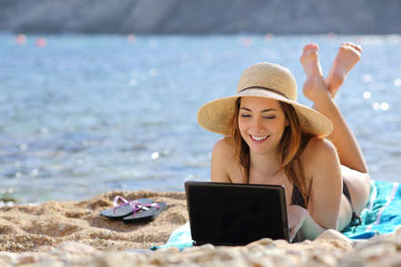 Woman on the beach browsing social media on a computer in summer with the sea in the background              Stock Photo