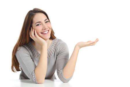 Mujer feliz que presenta con la mano abierta sosteniendo algo en blanco aislado en un fondo blanco