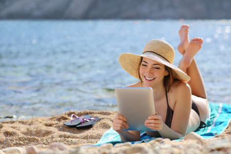 teen girl bikini: Pretty woman reading a tablet reader on the beach on vacations with the sea in the background