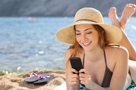 Woman on the beach texting a smart phone in summer with the sea in the background           photo