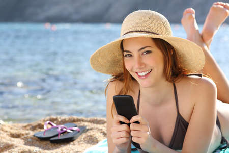 Woman texting in a smart phone on holidays on the beach with the sea in the background               Stok Fotoğraf