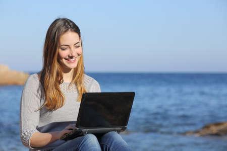 mujer mirando el horizonte: Muchacha feliz del adolescente navega los medios sociales en la playa con el mar de fondo