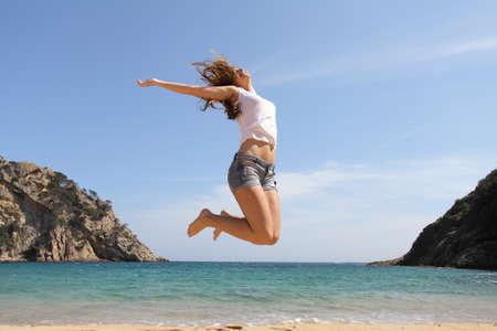 Adolescente feliz saltando en la playa con el océano en el fondo Foto de archivo