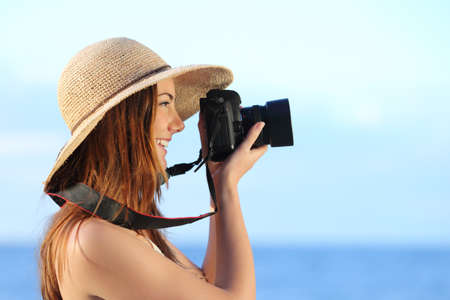 slr camera: Happy woman on vacation photographing with a dslr camera on the beach with the horizon in the background
