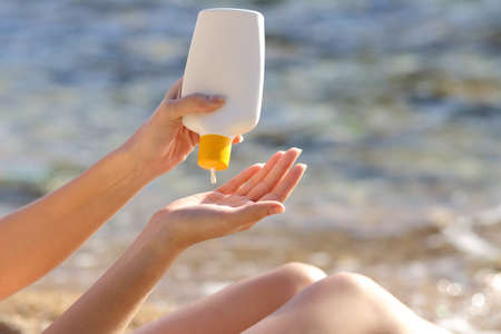 Woman hands putting sunscreen from a bottle on the beach with the sea in the background              photo