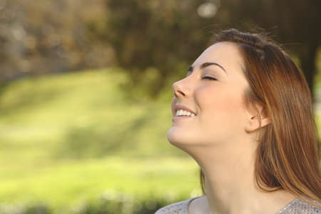 close: Beautiful happy smiling woman doing breathing deep exercises in a warmth park green background