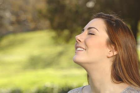 Mooie gelukkige glimlachende vrouw doet ademen diep oefeningen in een warmte park groene achtergrond