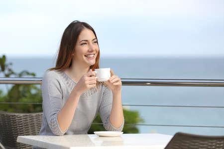 mujer tomando cafe: Mujer hermosa que sostiene una taza de café en un restaurante con el mar de fondo