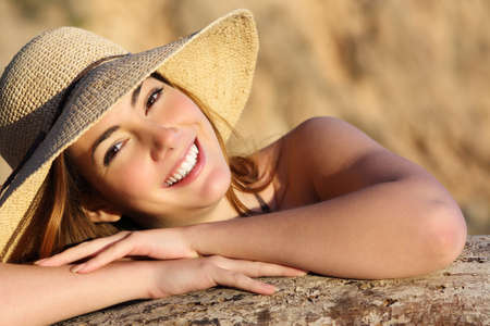 tooth whitening: Portrait of a happy woman smiling with perfect white smile with a warm light and background