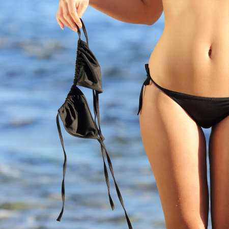 Close up of a woman on the beach in topless holding the bikini bra with the blue water in the background             Stock Photo