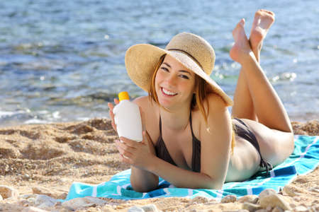 skin protection: Happy woman holding a sunscreen bottle lotion on the beach with the sea in the background