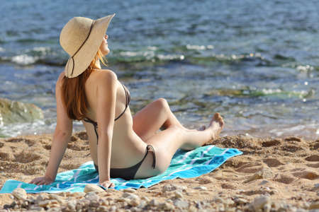 Woman sunbathing on the beach in summer with the sea in the background              photo
