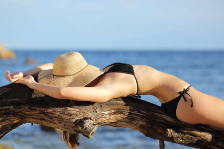 Fitness woman sunbathing on the beach sleeping with the sea  photo