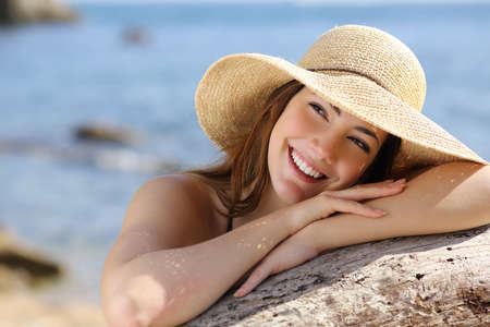 sideways: Happy woman with white smile looking sideways on vacations with the beach in the background