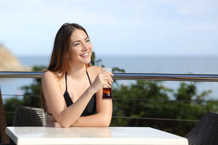 Woman on vacation drinking in a hotel terrace with the beach in the background photo