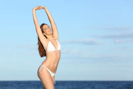 Fitness happy woman with perfect body on the beach with the sky and the sea in the background            photo