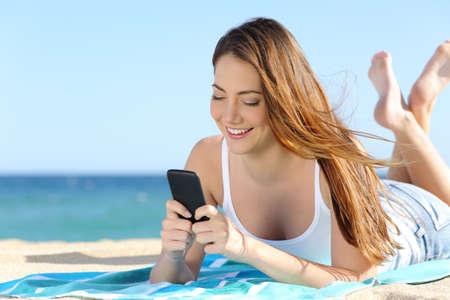백그라운드에서 바다와 수평선 해변에 누워 스마트 폰을 이용하여 예쁜 십 대 소녀 스톡 콘텐츠
