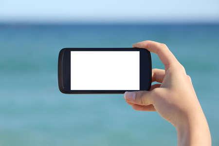 백그라운드에서 바다와 해변에 빈 스마트 폰 가로 화면 표시를 게재하는 여자 손