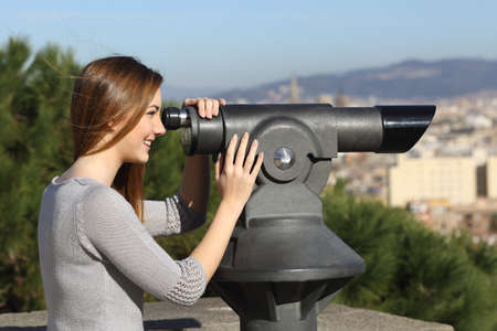 Tourist woman watching the city through a telescope photo