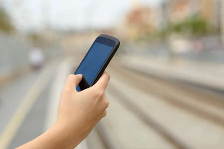 hand rails: Woman hand holding a smart phone in a train station with the rails  Stock Photo