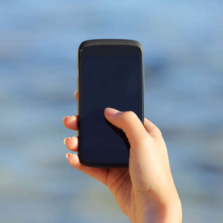 Woman hand holding and showing a blank smart phone screen on the beach with the sea photo
