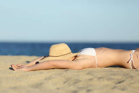 Woman resting sunbathing on the sand of the beach with a picture hat with the sea  photo