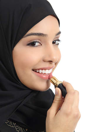 facial painting: Portrait of an arab saudi emirates woman painting her lips with a lipstick isolated on a white background              Stock Photo