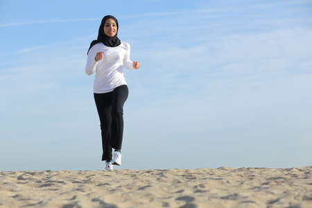 arabic: Front view of an arab saudi emirates woman running on the beach with the horizon in the background