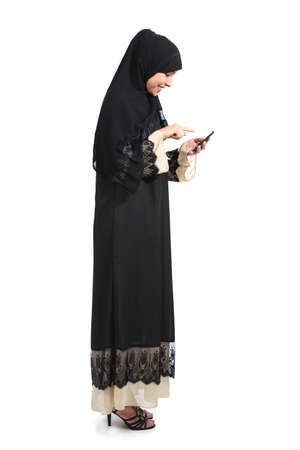 Full body of an arab saudi woman browsing a smart phone isolated on a white background                photo