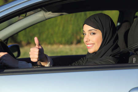 Gelukkig Arabische saudi vrouw besturen van een auto met duim omhoog lachend met een hoofddoek