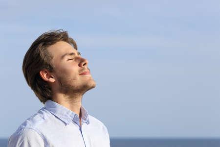 respiracion: Hombre joven feliz de respirar profundo con el horizonte en el fondo Foto de archivo