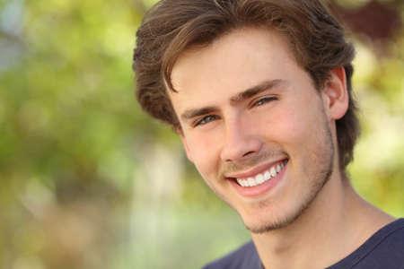 緑の背景で白の完璧な笑顔でハンサムな男の顔