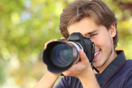 Photographer photographing and learning with a dslr digital camera with a green background                 Stock Photo
