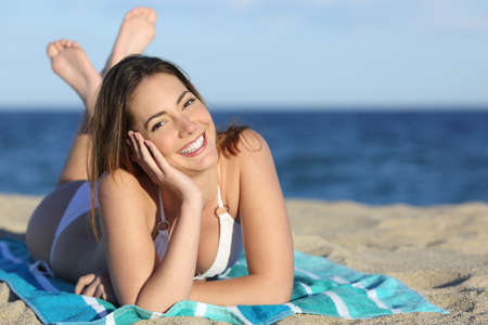 beach towel: Happy woman with white perfect smile resting on the sand of the beach and looking at camera