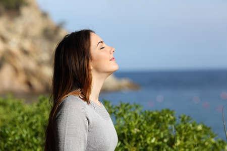 persona respirando: Mujer que respira aire puro relajado en vacaciones con la playa en el fondo Foto de archivo