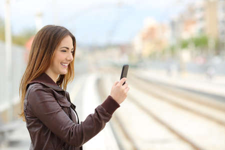 traveller: Happy woman browsing social media in a train station with the railways  Stock Photo