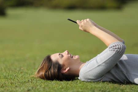 internet movil: Mujer que usa un tel�fono inteligente que descansa sobre la hierba en un parque con un fondo desenfocado Foto de archivo