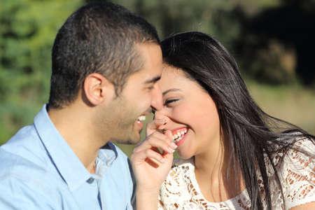 アラブのカジュアルなカップルの男と女いちゃつくと緑と公園で幸せな笑い