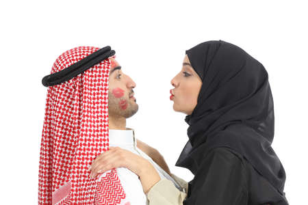 obsessed: Arab saudi obsessed woman kissing desperately a man isolated on a white background           Stock Photo