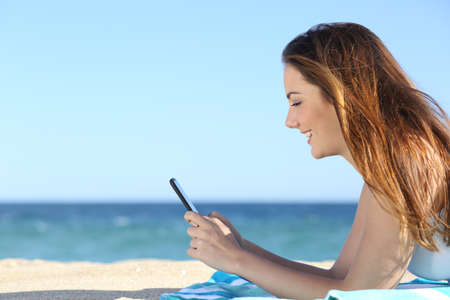 海とビーチでスマート フォンで女性のテキスト メッセージのプロファイル