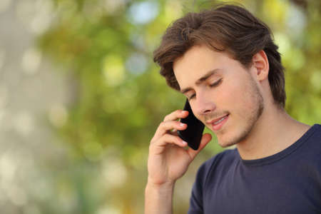 Handsome man talking on the mobile phone outdoor with green photo
