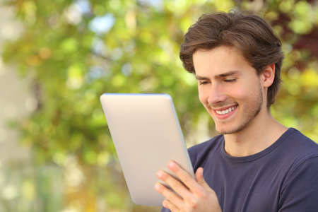 Happy man reading a tablet reader outdoors